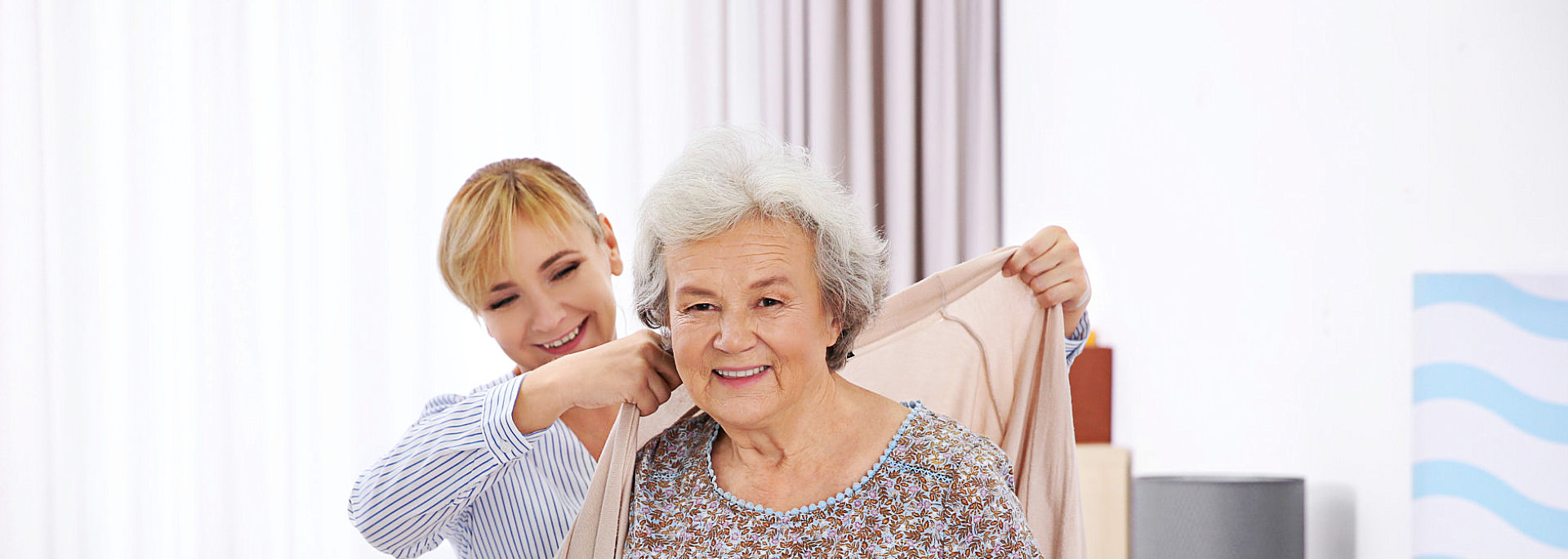 caregiver helping her patient to get clothes